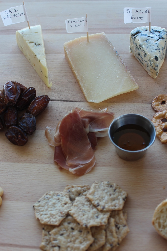 cheese plate, charcuterie board, variety of cheeses, grapes, prosciutto, crackers, nuts, bread, pretzels, honey, dates,
